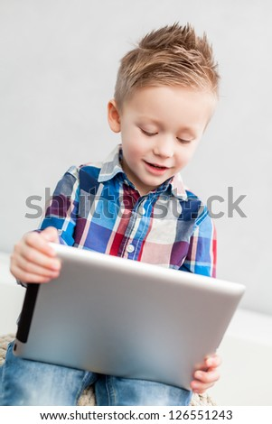 Boy sitting  in the living room using a tablet pc - stock photo