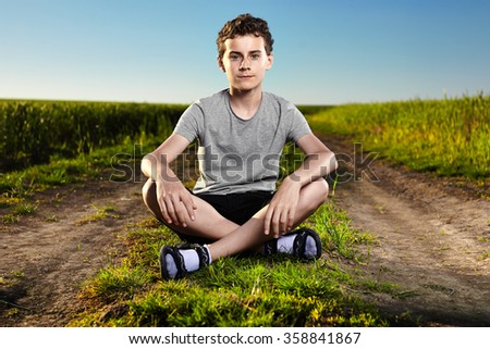Boy sitting in the middle of a countryside road - stock photo