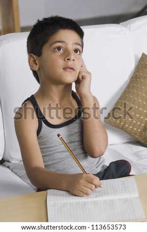 Boy sitting on a sofa and thinking - stock photo
