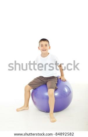 Boy sitting on big ball against white background - stock photo