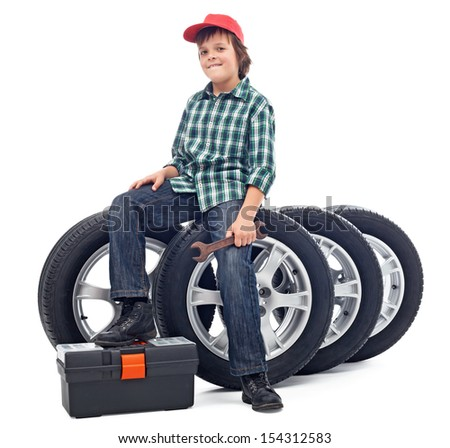 Boy sitting on car tires holding spanner - isolated - stock photo