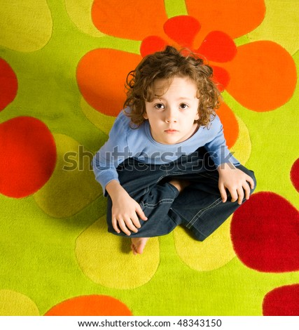 Boy sitting on colorful carpet - stock photo