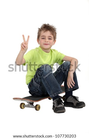 Boy sitting on skateboard - stock photo