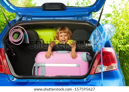 Boy sitting on the back sit with bags and other luggage in the car trunk happy and laughing ready to go on the trip - stock photo