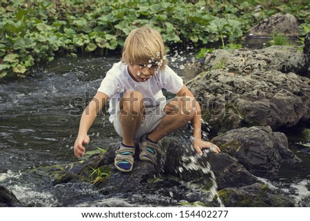 boy sitting on the stones near the river and playing with water - stock photo