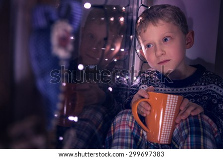 Boy sitting on window decorated for Christmas Eve - stock photo