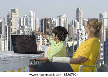 Boy sitting with woman pointing over balcony. Woman with cast and laptop on table. Horizontally framed photo. - stock photo
