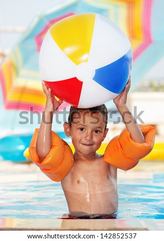 Boy smiling and playing with ball in to a swimming pool - stock photo