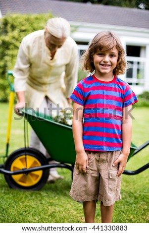 Boy smiling while standing against grandmother with wheelbarrow in yard - stock photo