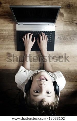 Boy spending time with notebook and modern technology - stock photo