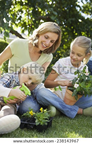 Boy Spraying Seedlings with Mother and Sister - stock photo