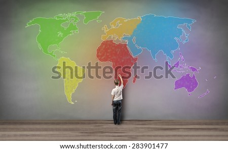boy standing and drawing world map - stock photo