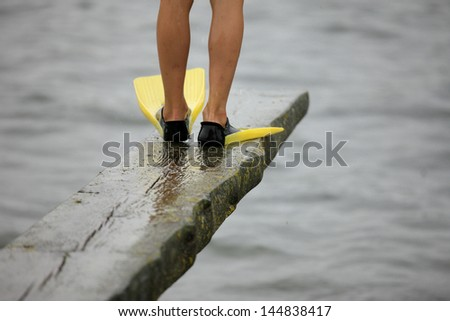 Boy standing and getting ready to dive - stock photo