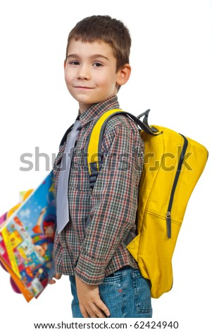 Boy  standing in profile holding bag and books and going to school in first day  isolated on white background - stock photo