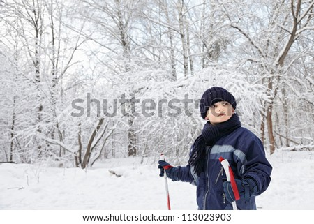 Boy standing in winter forest with ski poles and looking sideways - stock photo