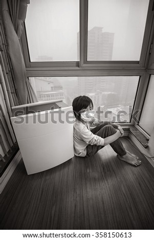 Boy staying home near air purifier on extremely polluted day - stock photo