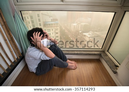 Boy staying home on extremely polluted day  - stock photo