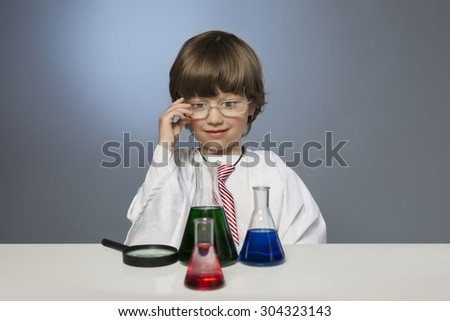 boy studying a substance in a test tube with a magnifying glass - stock photo