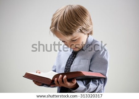 Boy studying and reading a book or bible isolated concept for education, religion or homework - stock photo