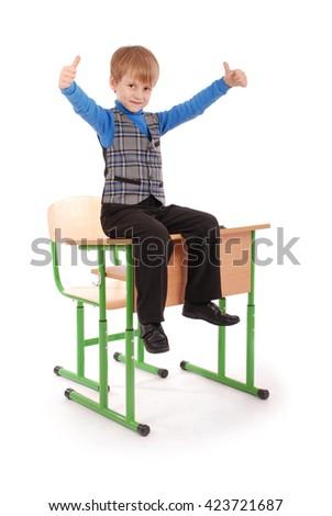 Boy Success. Boy sitting on the school desk isolated on white - stock photo
