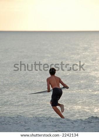 Boy surfer on the beach - stock photo