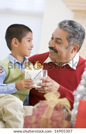 Boy Surprising Grandfather With Christmas Present - stock photo