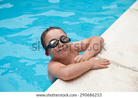 Boy swimming in a pool - stock photo