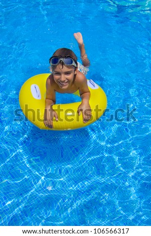boy swimming in pool on rubber ring - stock photo