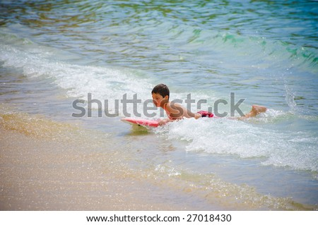Boy swimming on the surf board - stock photo