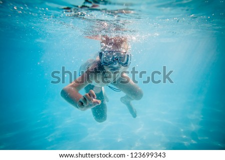Boy swimming under water in pool - stock photo