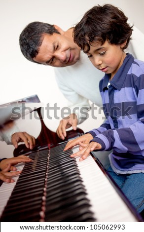 Boy taking piano lessons at home with a tutor - stock photo