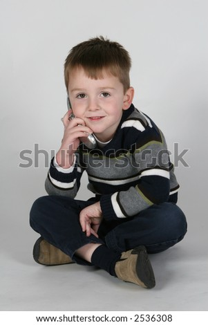 boy talking and smiling on cell phone - stock photo