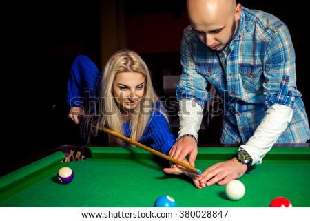 boy teaches girl how to hit in billiards. Billiard sport concept. American pool billiard. Pool billiard game. - stock photo