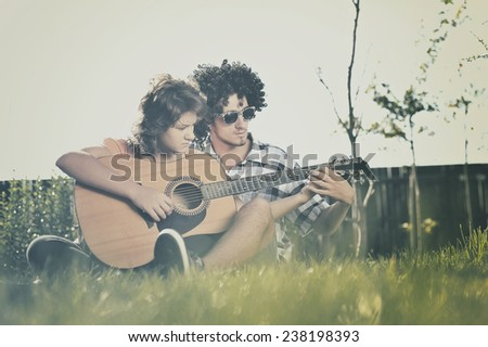 Boy teaches girl to play guitar - stock photo