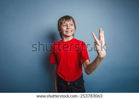 boy teenager European appearance in a red shirt showing thumbs digit three on a gray background, the score - stock photo