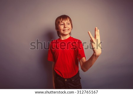 boy teenager European appearance in a red shirt showing thumbs digit three on a gray background, the score retro - stock photo
