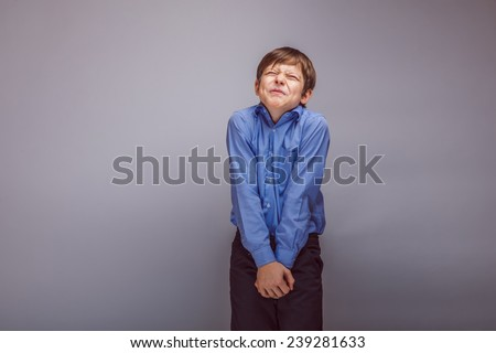 boy teenager European appearance winced from the pain in the groin on a gray background - stock photo