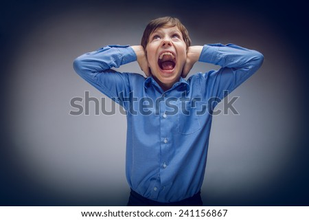 boy teenager of European appearance brown hair closed his ears shouting on gray background cross process - stock photo