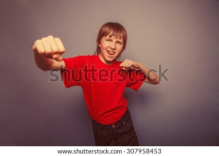 Boy, teenager, twelve his  red  in shirt, fists  red showing   years retro - stock photo