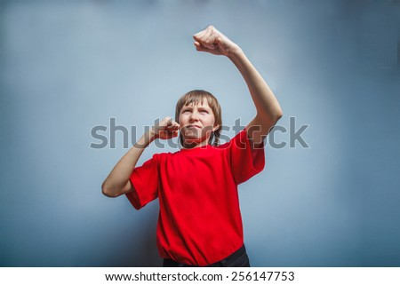 Boy, teenager, twelve years in a red shirt, showing his fists - stock photo