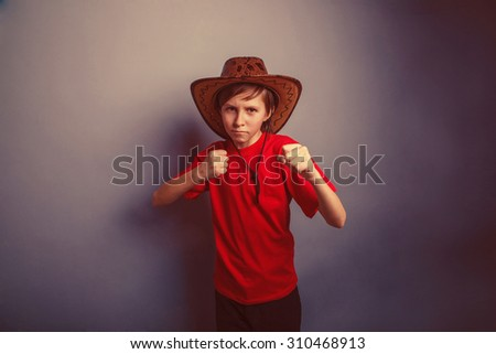 Boy, teenager, twelve years in red t-shirt with  cowboy hat showing sign yes retro - stock photo