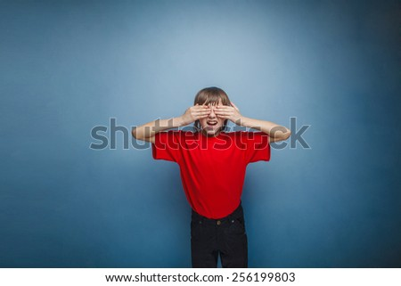 Boy, teenager, twelve years in the red shirt, closed his eyes, his hands - stock photo