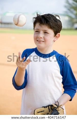Boy throwing baseball in air - stock photo