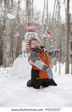 Boy throwing snowball in front of snowman - stock photo