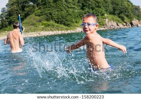 Boy toying creates large splashes in the sea. Focus on the splashes. - stock photo