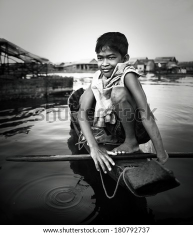 Boy Traveling by Boat in Floating Village, Cambodia - stock photo