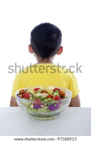 Boy turning his back to fruit and vegetable salad shot in studio isolated on white - stock photo