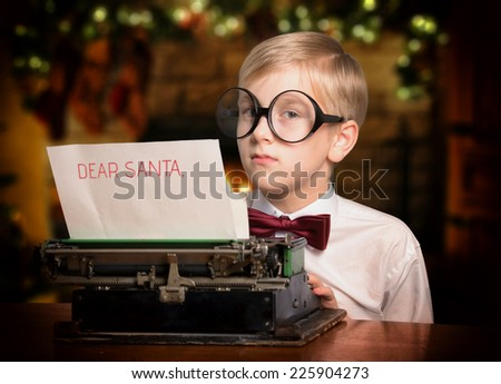 Boy typing on a typewriter a letter to Santa Claus - stock photo