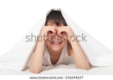 boy under the blanket look through his palms like binoculars - stock photo