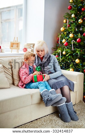 Boy unpacking Christmas present with grandma - stock photo